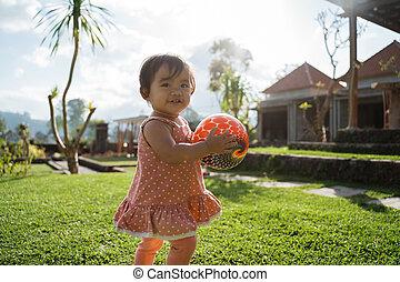 Little girl enjoyed playing ball in the backyard