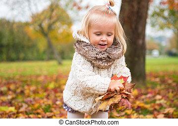 Little girl enjoying autumn in the park