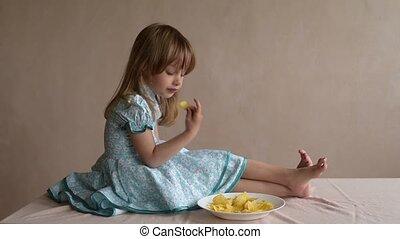 Little girl enjoying potato crisps