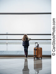 Little girl enjoying view from window at airport
