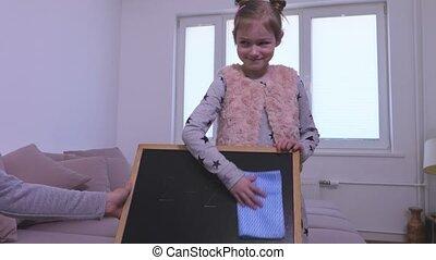Little girl erasing blackboard