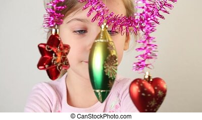 Little girl examine christmas-tree decoration, which hang.