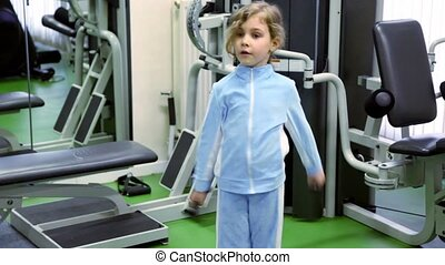 Little girl exercises with dumbbells at background of training equipment near mirror