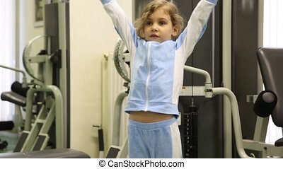 Little girl exercises with dumbbells at background of training equipment