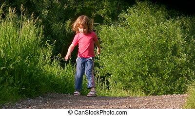 little girl exercising in summer forest