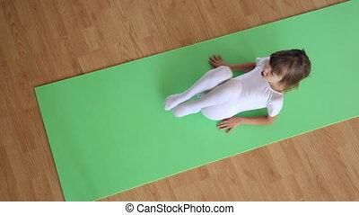 Little girl exercising on floor mat