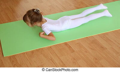 Little girl exercising on floor mat