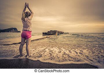 Little girl exercising on the beach