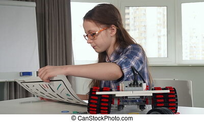 Little girl explores the instruction of construction set