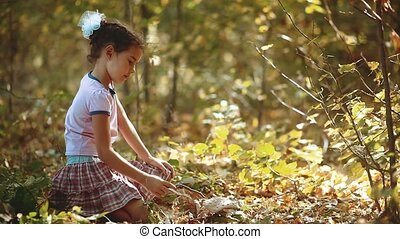 little girl exploring a mushroom in a green wild forest....