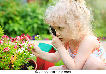 Little girl exploring nature with a magnifying glass