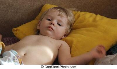 little girl falls asleep on a sofa