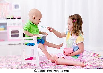 Little girl feeding baby brother
