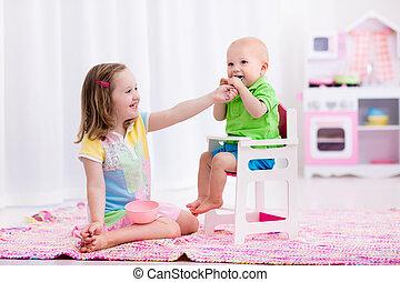 Little girl feeding baby brother - Cute little girl feeding...
