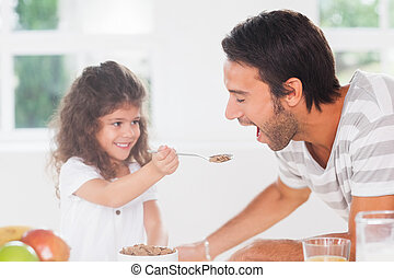 Little girl feeding cereal to father