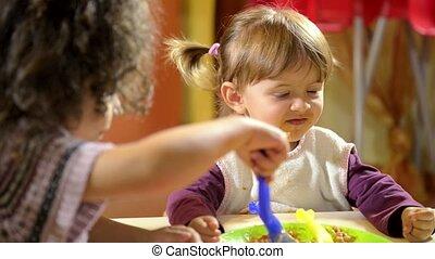 Little girl feeding her friend