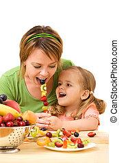Little girl feeding her mother