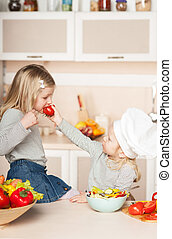 Little girl feeding her sister tomato while cooking salad