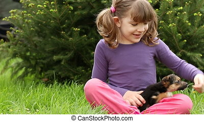 little girl feeding puppy