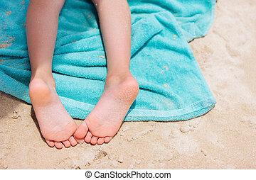 Little girl feet on a beach towel