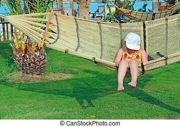 Little girl fell asleep swaying in hammock at tropical resort.