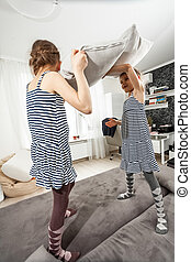 little girl fighting with pillows on bed
