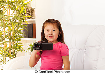 Little girl filming with camera