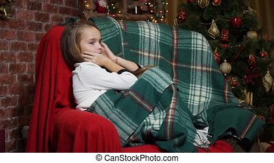 Little girl flirts sitting in a chair near a Christmas tree