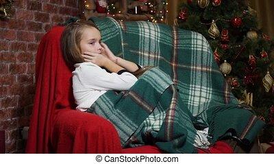 Little girl flirts sitting in a chair near a Christmas tree