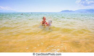 Little Girl Follows Thrown Ball from Mother to Sand Beach