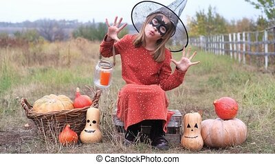 Little girl in halloween costume frightening while sitting on wooden box with pumpkins around in nature