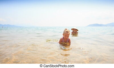 Little Girl Gambols on Sea Edge against Mom in Straw Hat