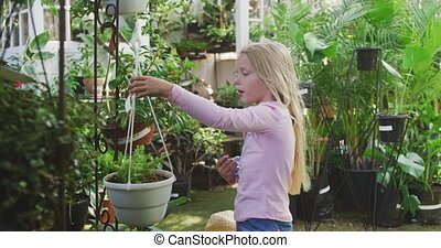 Little girl gardening in a greenhouse - Side view of a ...