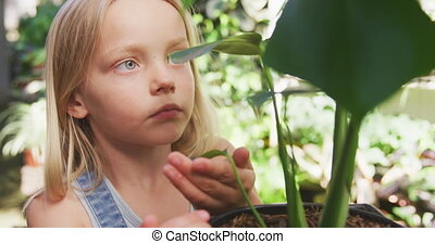 Little girl gardening in nature - Front view of a focused ...