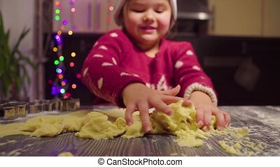 Little girl gathering dough from the table
