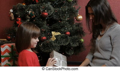 Little girl gets the christmas gift from her mother