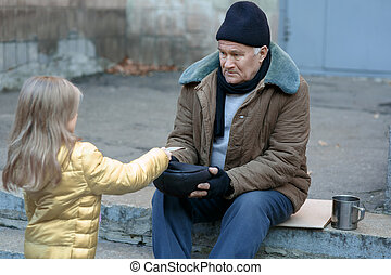Little girl gives money to the beggar.