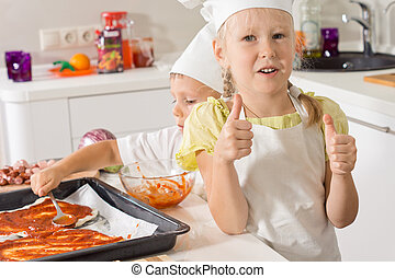 Little girl giving a thumbs up as she bakes pizza