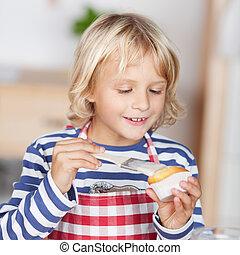Little girl glazing a cupcake - Cute little blond girl ...