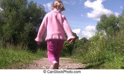 Little girl go back on path in park.