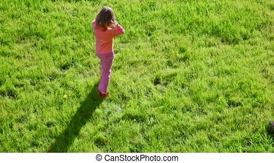 little girl going around on green grass