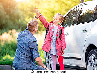 Little girl greeting father after school