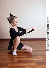 little girl gymnast sitting on the floor