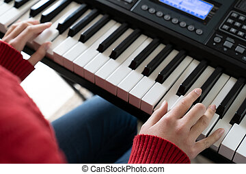 Little girl hand playing piano keyboard