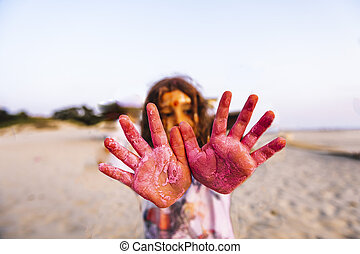 little girl hands covered with colored powder