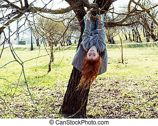 Little girl hanging upside down on a tree