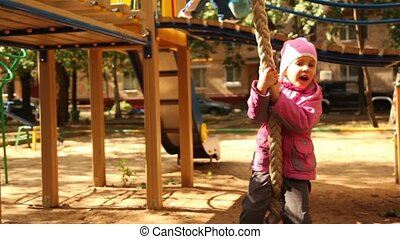 Little girl hangs on rope at playground and sway at sunny autumn day