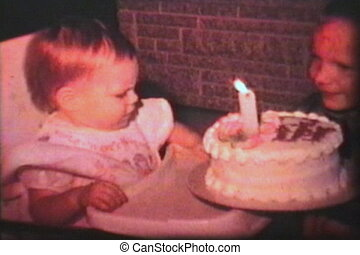 A little girl celebrates her first birthday and sticks her hand in the cake. (Scan from archival 8mm film)