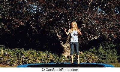 Little girl having bouncing on a tr