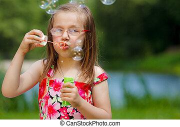 Little girl having fun blowing soap bubbles in park.